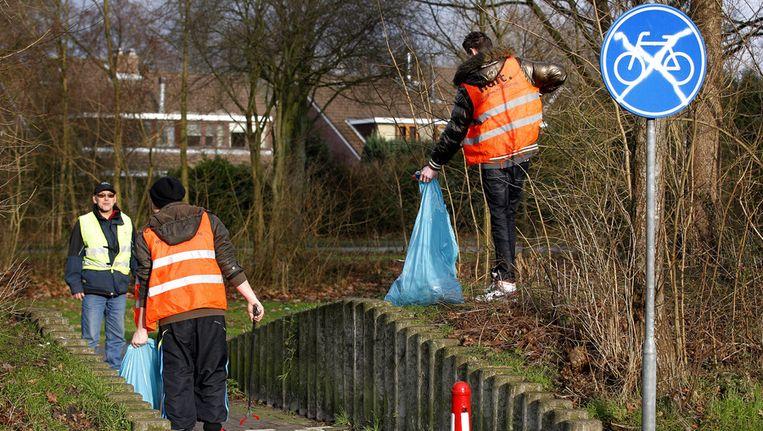 Jongeren voeren hun taakstraf, het opruimen van vuurwerkresten, uit voor een overtreding tijdens de jaarwisseling. Beeld anp