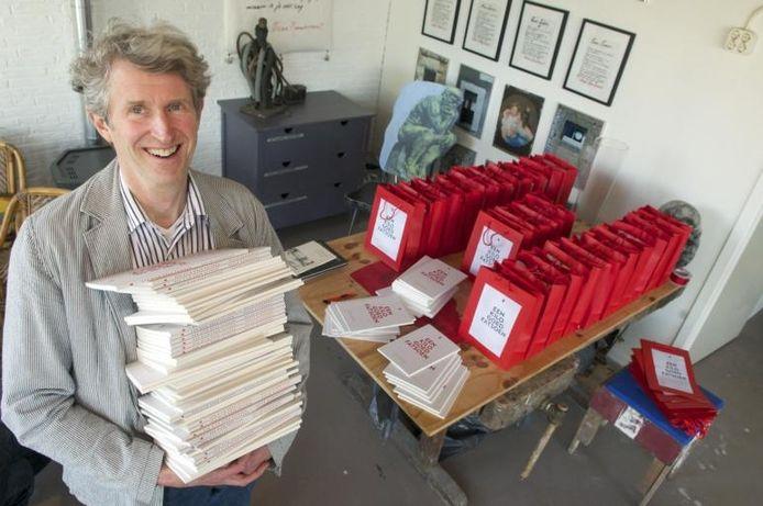 Oscar Rambonnet met in zijn handen een stapel dichtbundels. Foto Marc Pluim