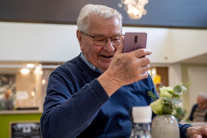 Jan van der Kieboom is maar wat blij met zijn nieuwe smartphone, waarmee hij nu kan beeldbellen met zijn dochter Karien.