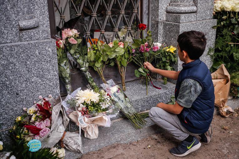 Een jongen brengt een bloem naar het graf van Aznavour in het Montfort l'Amaury kerkhof in West-Parijs.