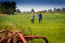Projectleider Bauke Zijlstra van de provincie Overijssel en ecologe Rosalie Martens van Natuurmonumenten lopen over grasland van een particuliere eigenaar die meewerkt aan de werkzaamheden in de Wieden.