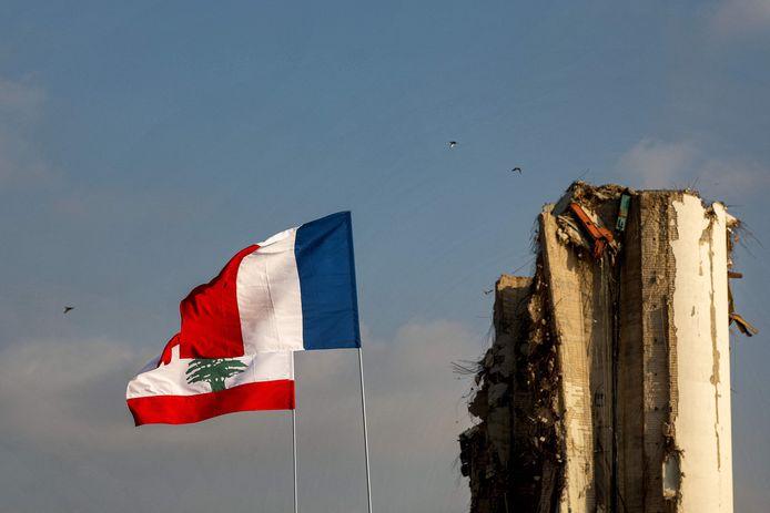 De vlaggen van Frankrijk en Libanon wapperen naast de verwoeste haven van Beiroet.