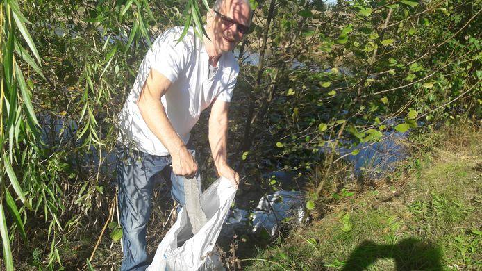 Meerhovenaar Tini Greveraars toont de inhoud van een zak afval, dat sterk doet denken aan asbest golfplaten.