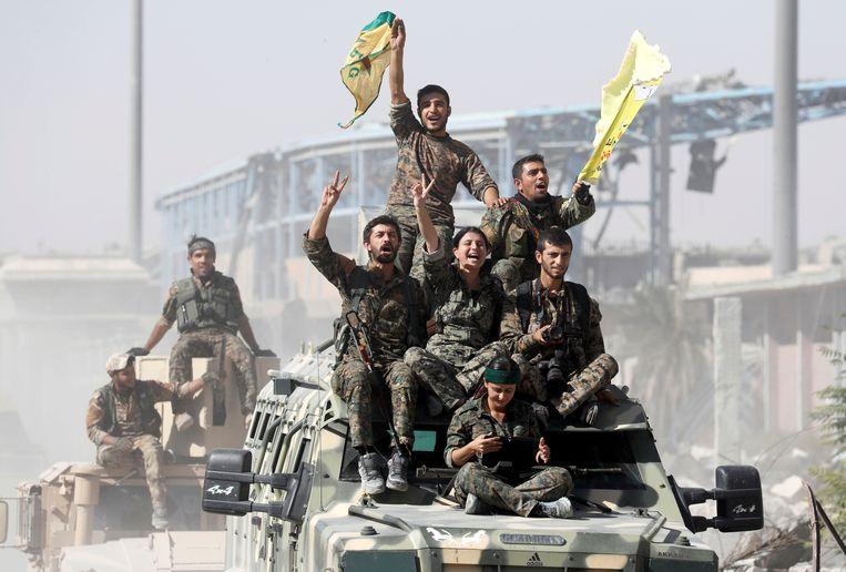 Soldaten van de Syrische Democratische Strijdkrachten (SDF) vieren de overwinning op IS in het Syrische Raqqa, in oktober 2017. Beeld REUTERS
