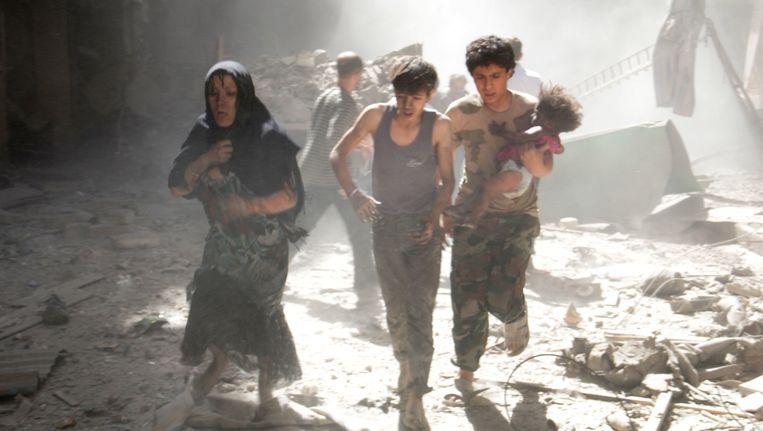 Vrouwen en kinderen vluchten na een aanval met een vatenbom in Aleppo.