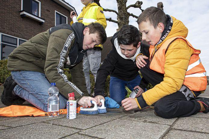Leerlingen poetsen Stolpersteine in Holten. Vandaag is het 76 jaar geleden dat Holten werd bevrijd.