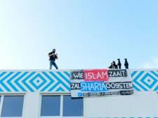Mannen protesteren op dak nieuwe islamitische school