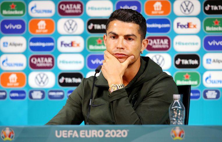Geen cola van de sponsor, maar water voor Ronaldo tijdens de persconferentie. Beeld Handout via REUTERS