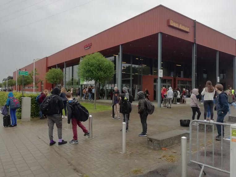 Leerlingen wachten bij Den Amer om te worden opgehaald.