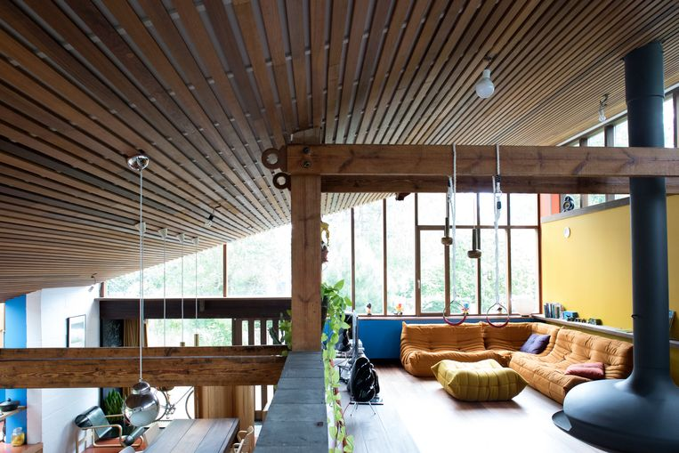 Het zachthellend houten plafond verbindt de keuken, eetkamer en woonkamer over de  verschillende niveaus. Beeld Karen Van Winkel