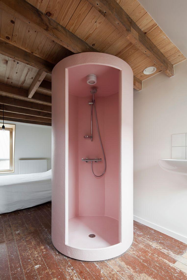 De ronde douche van roze polyester werd in het midden van de slaapruimte geplaatst om de vier hoeken vrij te houden. Beeld Johnny Umans