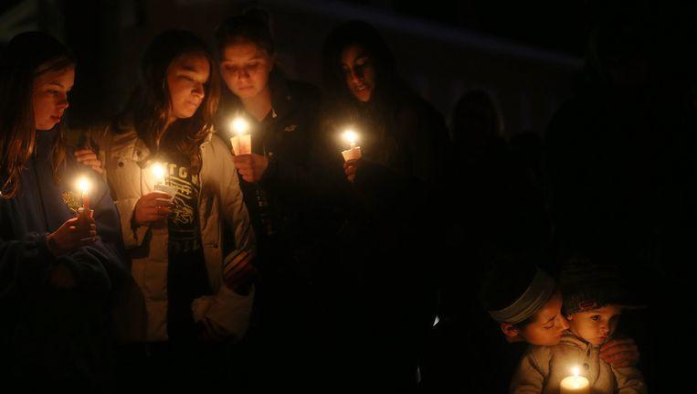 Mensen branden kaarsen om de slachtoffers van de schietpartij op Sandy Hook te herdenken Beeld ANP