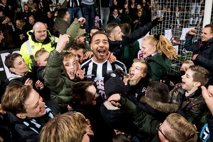 Jonge fans van Heracles vieren na de zege op Ajax feest met Cyriel Dessers.