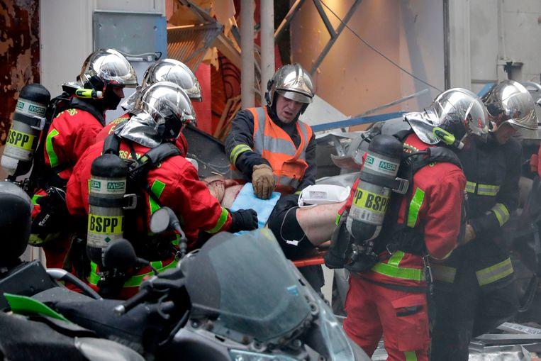 Een gewonde man wordt weggevoerd na de explosie in een bakkerij in Parijs. Beeld AFP