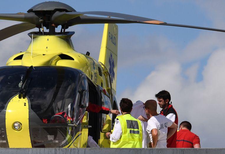 Chris Froome wordt aan boord gebracht van een helikopter na zijn zware val. Beeld AFP