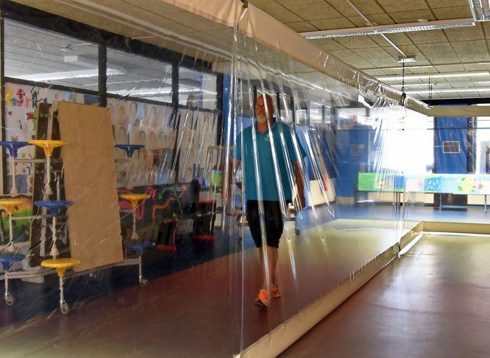 Concierge Sjoerd van Helmond van het Lodewijk College in Terneuzen loopt door de gang die afgescheiden is met plastic. Eenrichtingverkeer was hier niet mogelijk.