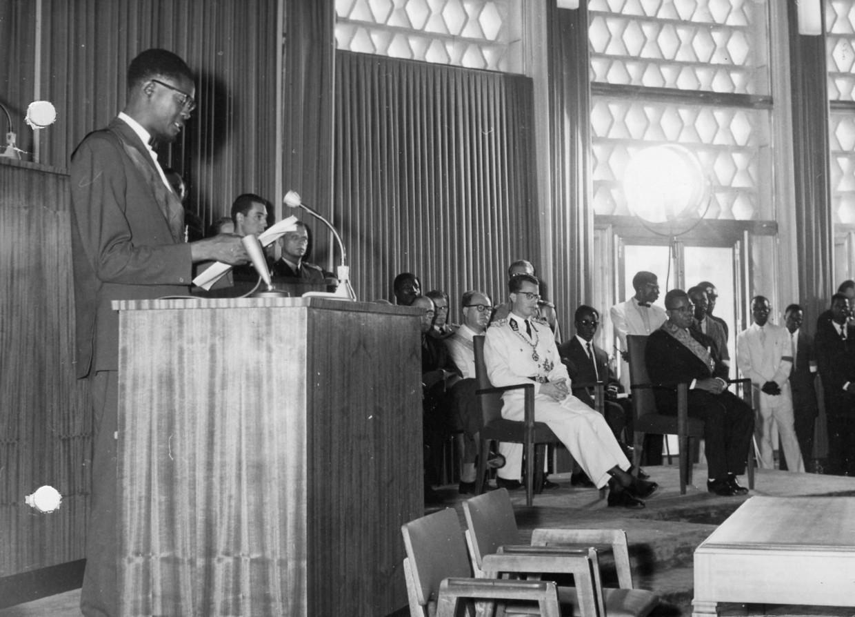 Onaangekondigd bestijgt premier Patrice Lumumba op 30 juni 1960 het spreekgestoelte. Koning Boudewijn (in het wit), die even eerder nog 'het genie van Leopold II' prees, weet niet wat er gebeurt.  Beeld Belga