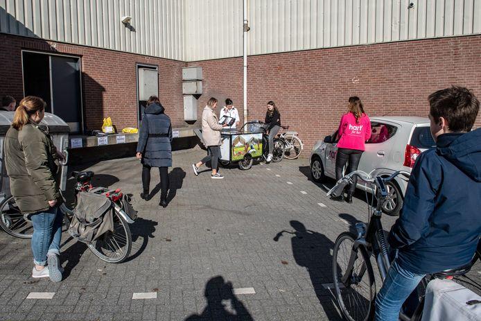 Vrijwilligers halen achter de Wijchense Hema pakjes op om te bezorgen.