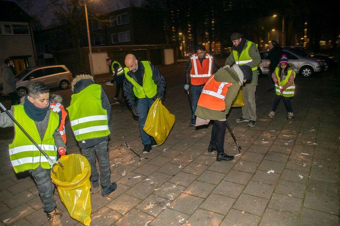 Met grijpstokken, bezems en vuilniszakken ruimen de Ahmadi-moslims de vuurwerkresten op in Tilburg Noord