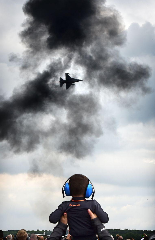 Jongetje met gehoorbescherming ziet hoe een F-16 over raast.  Beeld Marcel van den Bergh / de Volkskrant