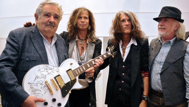 Jose Mujica, president van Uruguay, ontvangt een gesigneerde gitaar van Aerosmith-leden Steven Tyler, Joe Perry (midden) en Brad Whitford (rechts). Foto uit 2013. Beeld AFP