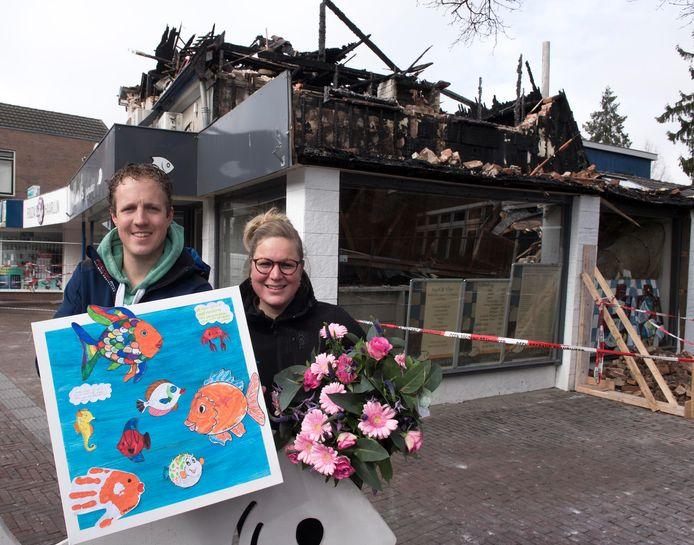 Dennis Tijssen en Nienke Rietberg Rietberg met bloemen en schilderwerk die zij daags na de brand ontvingen als steun in de rug.