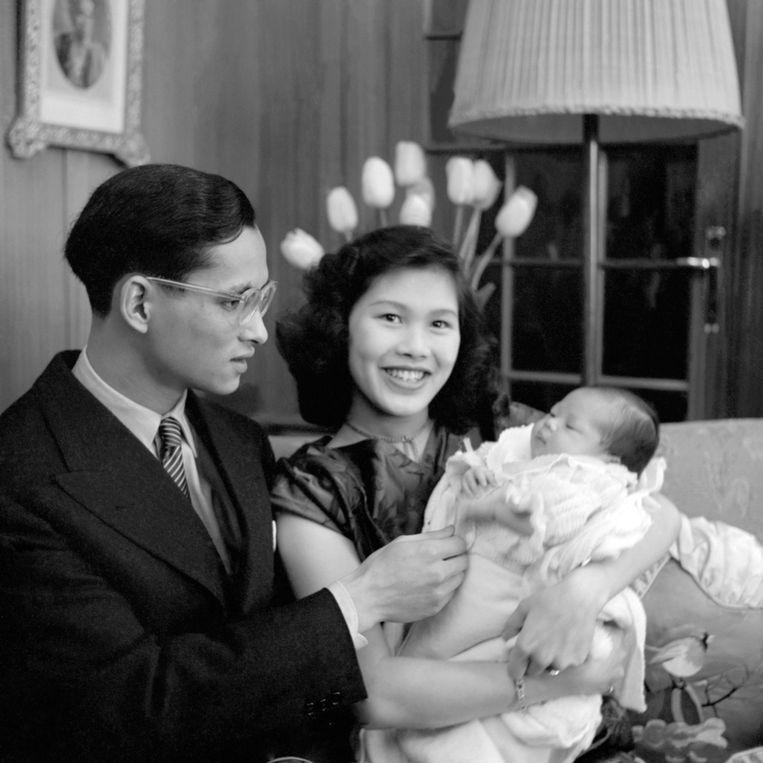 Een jonge koning Bhumibol met koningin Sirikit en hun eerste kind, princes Ubol Ratana. Beeld AFP