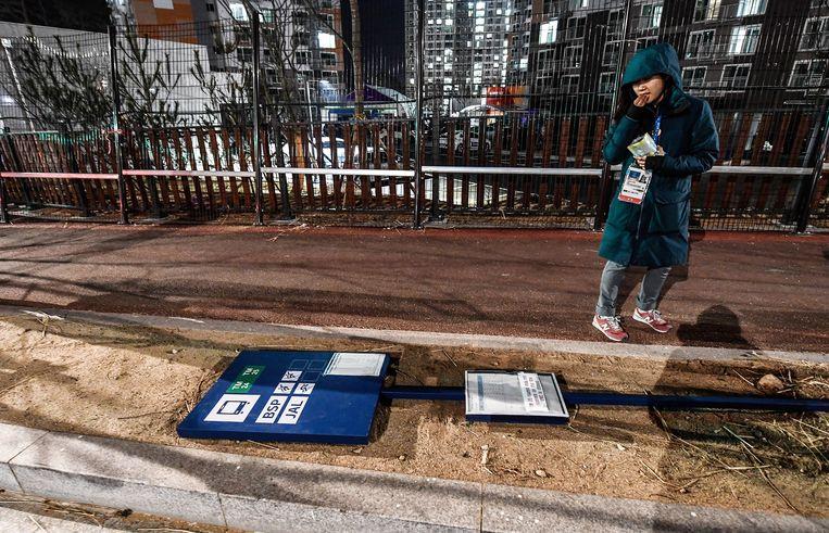 Een vrouw in het olympisch dorp van Pyeongchang kijkt naar een omvergeblazen aanwijzingsbord. Beeld EPA