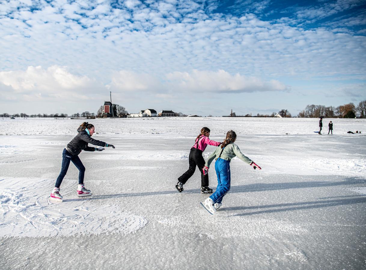 Kinderen schaatsen in de uiterwaarden bij Alphen.