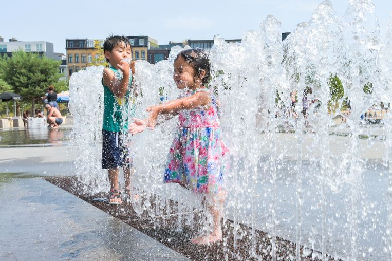 Mensen zoeken verkoeling in Park Spoor Noord op de warmste dag ooit. Beeld Patrick Hattori