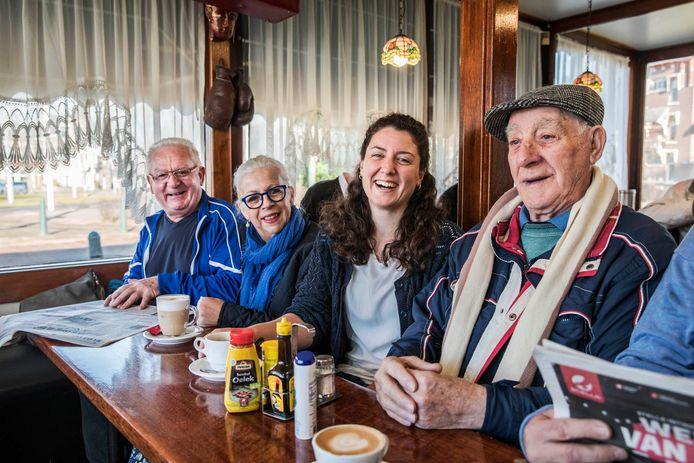 Milene van Arendonk (midden) in gesprek in koffiehuis 't Statenplein. Daarnaast foto's van Milene uit haar boek.