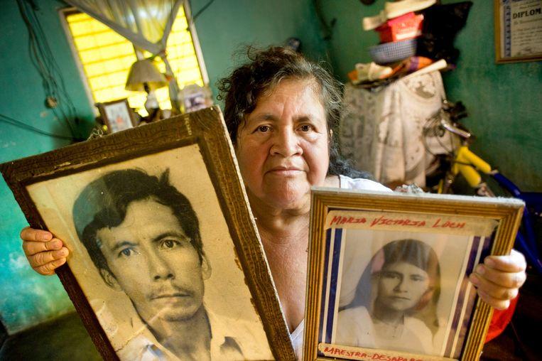 Alejandra Ramírez met in haar armen de portetten van haar man Isidro Loch en schoonzus María Victoria Loch. Beiden verdwenen en er werd nooit meer iets van ze vernomen. Beeld Piet den Blanken
