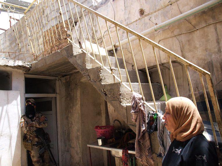 Samira Younis in haar beschadigde huis, met een van de militairen die de stad bewaken.  Beeld Judit Neurink