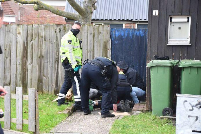 Politieagenten houden de via Burgernet gezochte gevaarlijke man in bedwang.