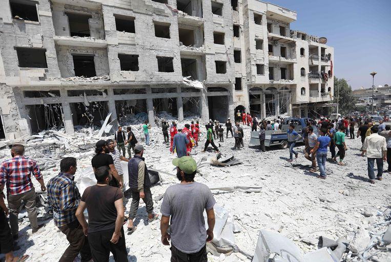 Syriërs komen begin augustus samen op de plek waar een autobom is afgegaan in de stad Idlib, en van laatste vier de-escalatiezones van het land waar de rebellen nog sterk aanwezig zijn.  Beeld AFP