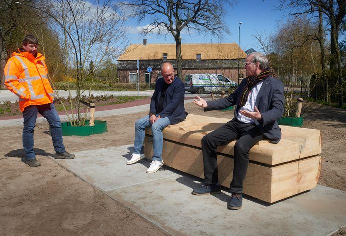 Wethouder Rein van Moorselaar (rechts) op de nieuwe bank. Naast hem buurtvertegenwoordiger Peter Sleegers en links Mark van der Leest, ambtelijk projectleider van de reconstructie Graafsebaan.