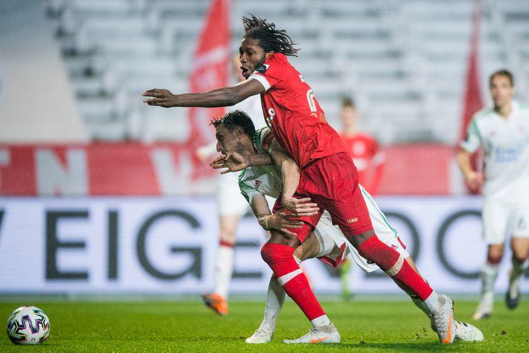 OHL-verdediger Sascha Kotysch heeft alle moeite met Dieumerci Mbokani op de Bosuil. Beeld BELGA
