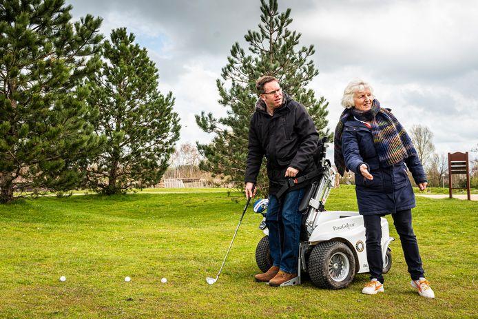 Nick van Yperen (links) en Marianne Waling kijken de bal na die Nick net sloeg. Nick is deels verlamd, maar hij kan overeind dankzij de Paragolfer, een elektronische rolstoel met lift.