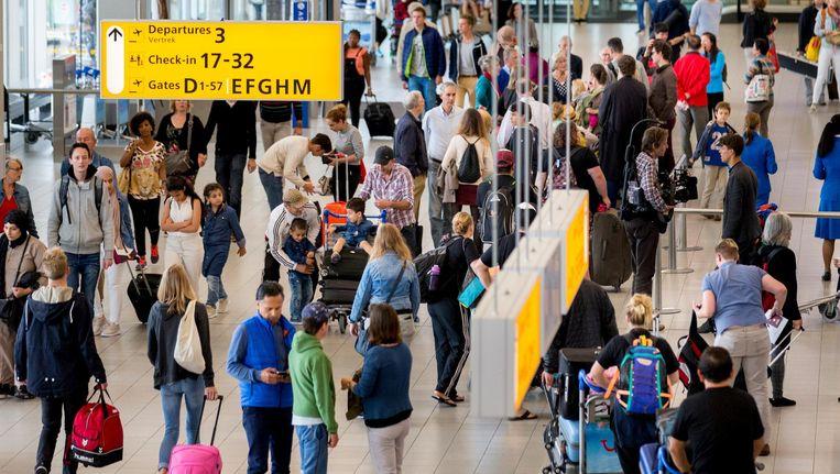 Passagiers in de vertrekhal tijdens de drukste dag van het jaar op luchthaven Schiphol Beeld anp