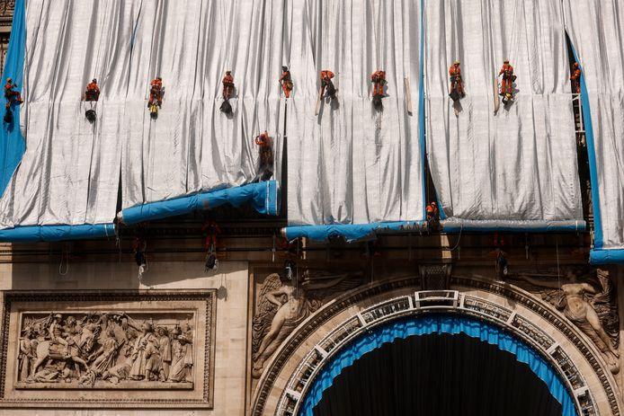 De abseilers gaan precies te werk om de Arc de Triomphe volledig in te kunnen pakken zonder het gebouw te beschadigen.