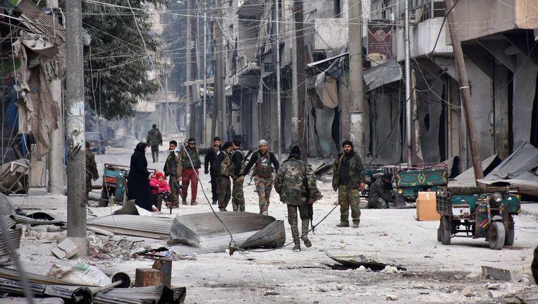 Syrische troepen lopen door al-Salihin nadat ze de buurt in het oosten van Aleppo hebben heroverd van rebellen. Beeld AFP