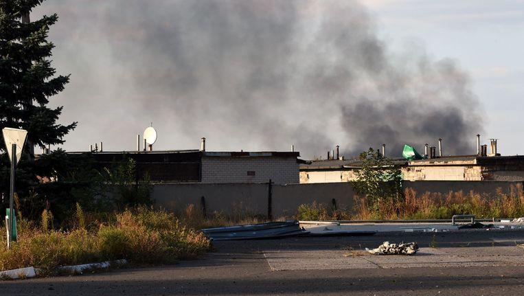 Een rookpluim boven het internationale vliegveld van Donetsk, waar regeringstroepen in gevecht zijn met separatisten. Beeld afp