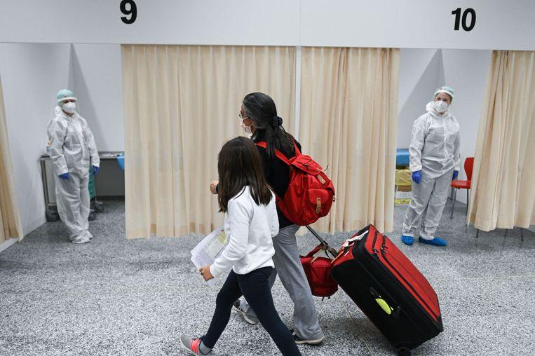 Passagiers uit New York gaan bij aankomst op het vliegveld van Milaan eerst langs de teststraat. Beeld AFP