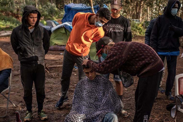 Een migrant laat zijn haar knippen in opvangkamp Las Raíces op het Canarische eiland Tenerife. Beeld Getty Images