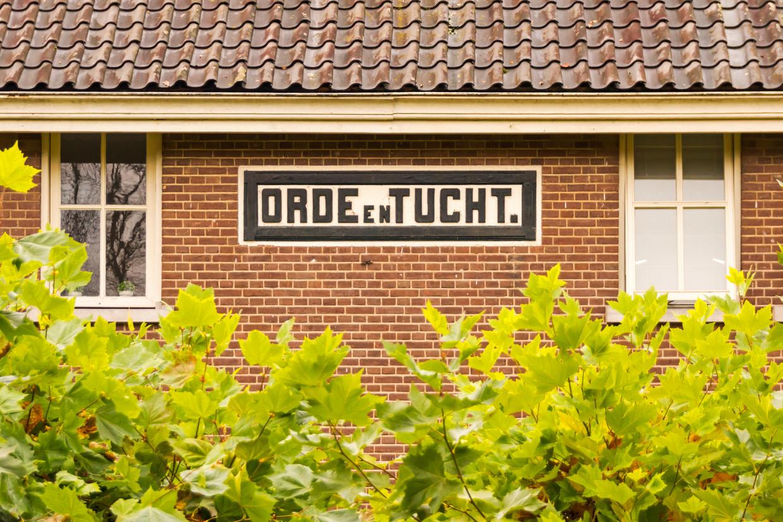 De gevelstenen van de huizen zeggen iets over de bewoners: hier woonden de officieren van de strafkolonie Veenhuizen. Beeld Sander Groen