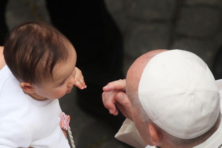 Paus Franciscus groet een kind tijdens zijn wekelijkse audiëntie op de binnenplaats van San Damaso.  Beeld Reuters