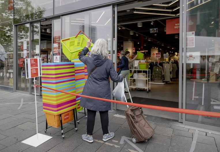Klanten pakken schoongemaakte mandjes voor de deur van de HEMA in Eindhoven. Beeld ANP