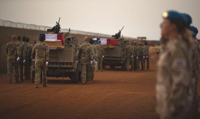 Militaire voertuigen vervoeren de kisten met daarin de lichamen van de omgekomen 29-jarige sergeant der 1e klasse Henry Hoving en de 24-jarige korporaal Kevin Roggeveld tijdens een ceremonie op het vliegveld van Gao in Mali. Beeld ANP