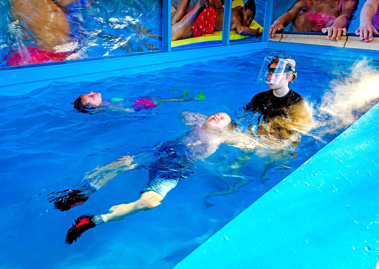 Saar (6) uit Puttershoek en Chayenna (5) uit Barendrecht zwemmen af in een omgebouwde zeecontainer.