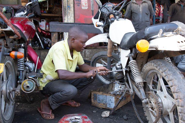 Jongeren in Burundi leren hun eigen geld te verdienen, bijvoorbeeld met het repareren van motoren. Beeld Erwin Alejo
